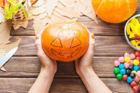 Female hands holding pumpkin with drawing Jack-o-lantern sketch near autumn leaves and colorful candies at wooden table.