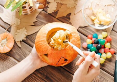 Woman preparing jack-o-lantern at wooden table for Halloween holiday. Female hands take out seeds from a pumpkin.