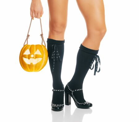 Halloween witch holding jack-o-lantern pumpkin on a white background. View of female legs in black shoes and knee socks.