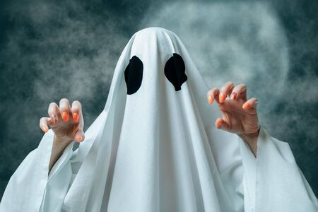 Unrecognizable woman in costume of white ghost with spooky gesture in Halloween full moon night.