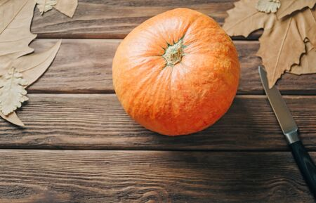 Pumpkin and knife near autumn leaves on wooden table, preparation to Halloween holiday. Top view. Stok Fotoğraf