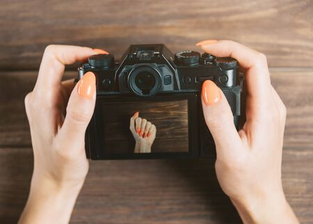 Unrecognizable woman holding photo camera with image of hand with bright orange manicure on screen. Point of view in first person.