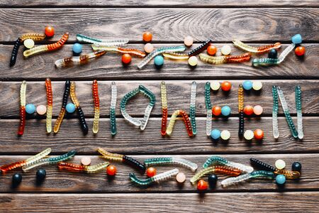 Word Halloween from colorful jelly candies on a wooden background, top view. Stok Fotoğraf