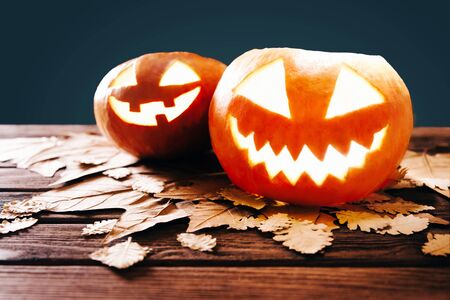 Two glowing jack-o-lantern pumpkins with autumn leaves on a wooden background, Halloween decoration.