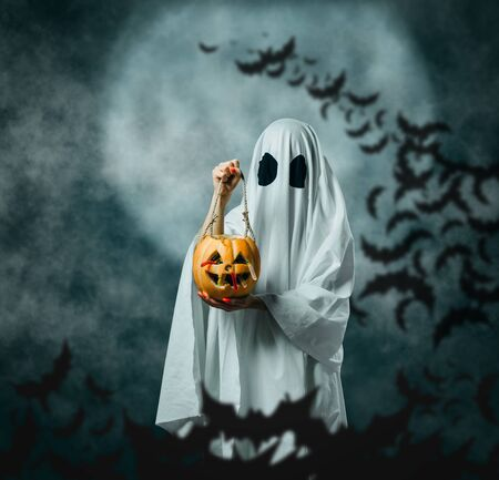 White ghost holding carved pumpkin with candies in Halloween night on background of full moon and flock of bats. Trick or treat.