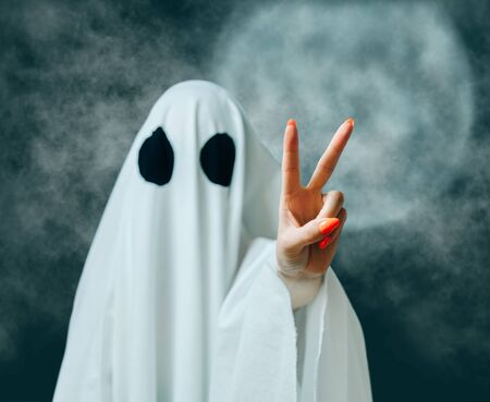 White ghost with black eyes showing peace sign gesture in Halloween full moon night.