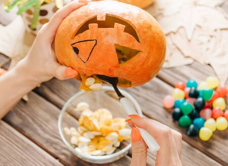 Female hands preparing jack-o-lantern for Halloween holiday. Woman take out seeds from a pumpkin.