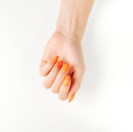 Woman's hand with autumn stylish orange color manicure on a white background.