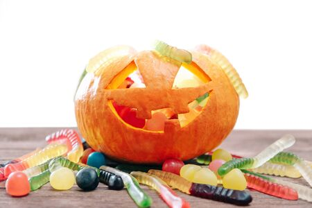 Trick-or-treat jack-o-lantern carved pumpkin basket with colorful jelly and candies for Halloween holiday. Stok Fotoğraf
