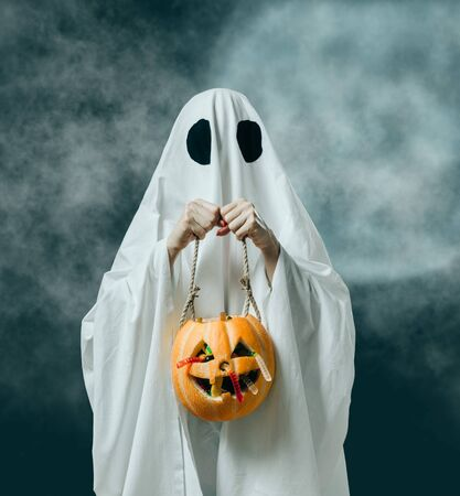 Woman in costume of white ghost sheet holding pumpkin basket with candies in Halloween night, trick or treat.