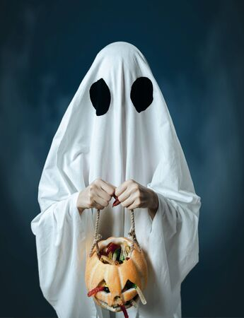 White ghost holding carved pumpkin with candies on a dark background. Trick or treat, Halloween concept.
