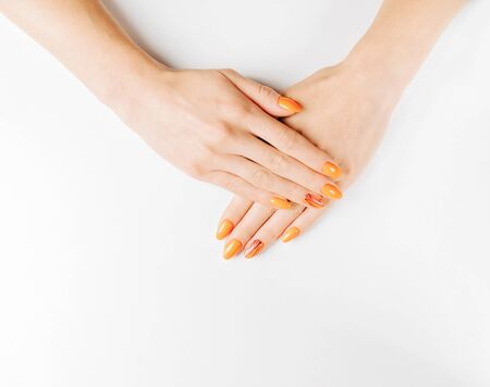 Female hands with beautiful professional manicure of orange color and geometric art-design on a white background.