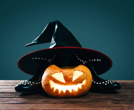 Halloween lighting pumpkin jack-o-lantern near witch outfit: black shoes and hat on a dark background.