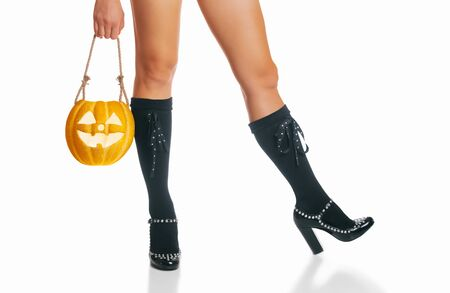 Unrecognizable woman in costume of witch holding glowing pumpkin near her legs in black shoes and knee socks. Halloween concept. Stok Fotoğraf