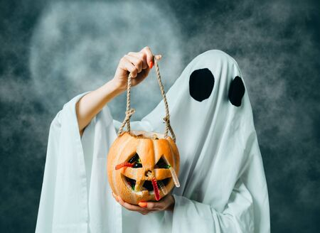 White ghost holding pumpkin jack-o-lantern basket with jelly for Halloween trick-or-treat tradition.