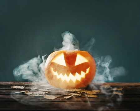 Halloween glowing jack-o-lantern pumpkin with smoke or fog on wooden table with autumn leaves.