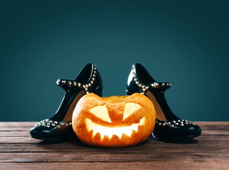 Halloween glowing carved pumpkin near black witch shoes on a dark background.
