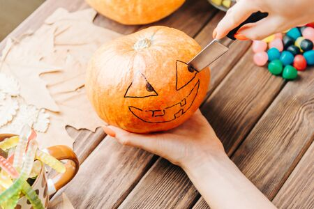 View of female hands carve with knife a pumpkin at wooden table, preparation for Halloween holiday. Traditional decoration jack-o-lantern. Stok Fotoğraf