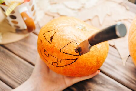 Female hand holding pumpkin with drawing Jack-o-lantern sketch and knife, process preparation to Halloween holiday.