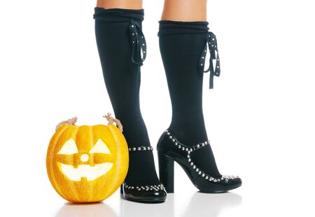 Halloween glowing jack-o-lantern pumpkin near female legs in black half-hose and shoes. Stok Fotoğraf