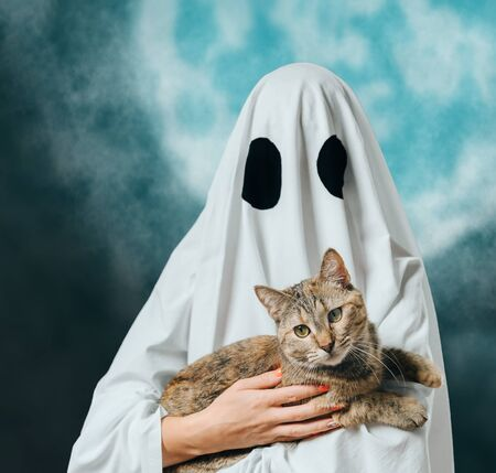 Woman  in costume of white ghost holding a ginger cat on background of moon. Halloween concept.