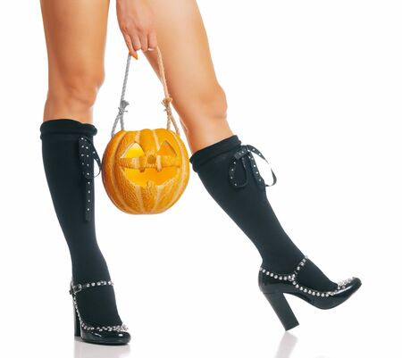 Halloween witch holding pumpkin trick-or-treat  basket near her legs in black shoes and knee socks.
