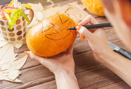 Woman drawing a face sketch on pumpkin decoration for Halloween holiday, view of hands.
