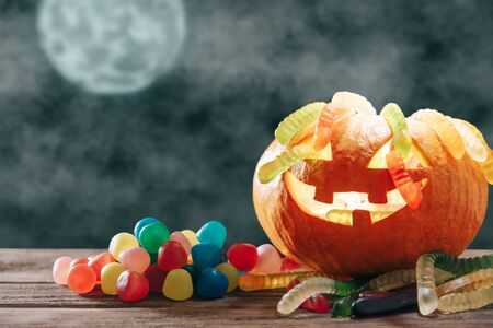Trick-or-treat jack-o-lantern carved pumpkin basket with colorful candies  and jelly in Halloween full moon night.