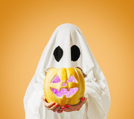 Halloween cute white ghost holding glowing jack-o-lantern pumpkin on yellow background. Stok Fotoğraf