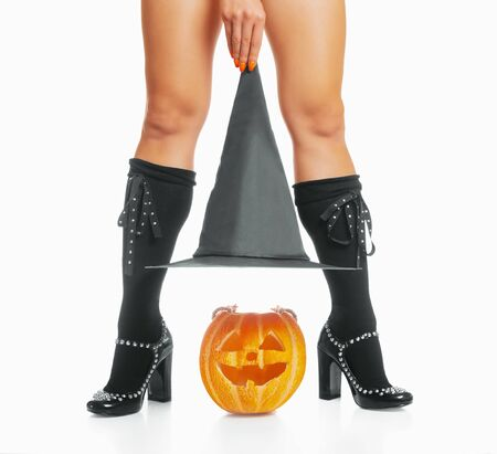 Unrecognizable woman in costume of witch holding a hat over carved pumpkin near her legs. Halloween concept.