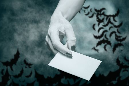 Dead hand giving blank white card in spooky Halloween night. Copy-space. Stok Fotoğraf