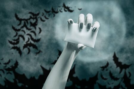 Dead hand with blank white card in front of full moon night and flock of bats. Copy-space. Halloween. Stok Fotoğraf