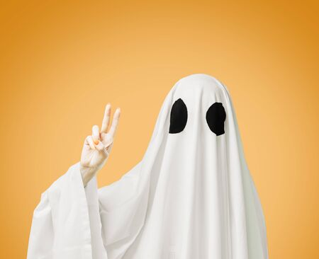 Halloween costume sheet white ghost with black eyes showing peace sign gesture on yellow background.