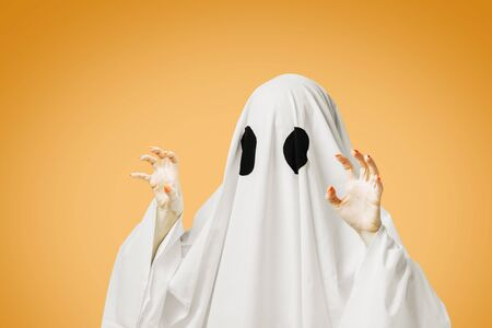 Cute white ghost with black eyes doing spooky gesture in Halloween on orange background.