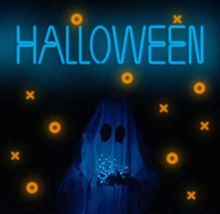 White ghost holding led garland on dark background neon sign Halloween. Stok Fotoğraf