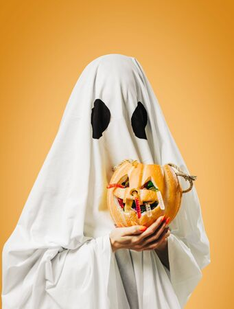 White ghost holding jack-o-lantern pumpkin basket with sweet candy in Halloween.