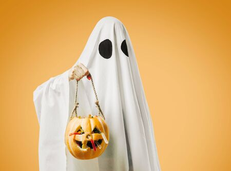 White ghost holding jack-o-lantern pumpkin basket with sweet candy in Halloween on orange background, trick-or-treat.