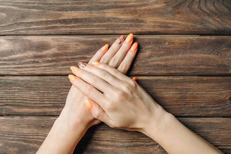 Female hands with beautiful professional manicure of orange color autumn stylish and geometric art-design on a wooden background. Point of view.