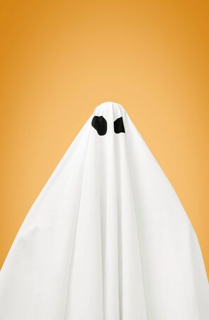 Abstract white ghost with black eyes on orange background. Halloween costume from sheet. Stok Fotoğraf