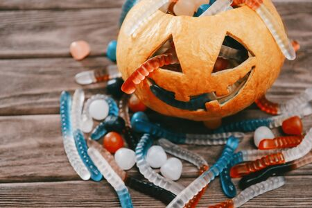 Trick-or-treat carved pumpkin basket with sweet jelly and candy in form of worms for Halloween holiday. Stok Fotoğraf