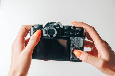 Woman's hands using digital photo camera with empty screen, copy-space. Point of view in first person. Stock Photo