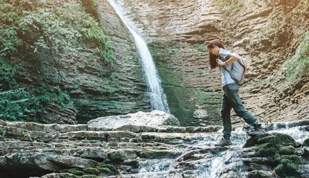 Traveler backpacker young woman crossing mountain creek in front of tall thin waterfall. 版權商用圖片