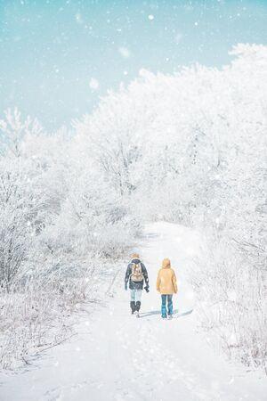 Couple de voyageurs marchant dans le beau givre et la forêt enneigée en hiver en plein air, vue arrière.