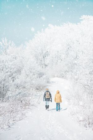 Traveler couple walking in beautiful frost and snowy forest in winter outdoor, rear view.