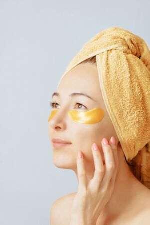 Portrait of a beautiful smiling young woman in a towel tied on her head and with collagen golden mask patches under her eyes. Beauty fresh smooth facial skin.