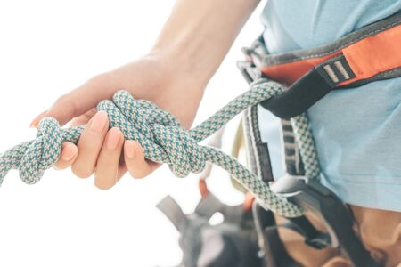 Sporty woman climber in safety harness holding rope knot eight on a white background, close-up. Standard-Bild