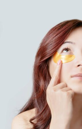 Half face portrait of beautiful young woman with golden under eye patch for healthy fresh skin.