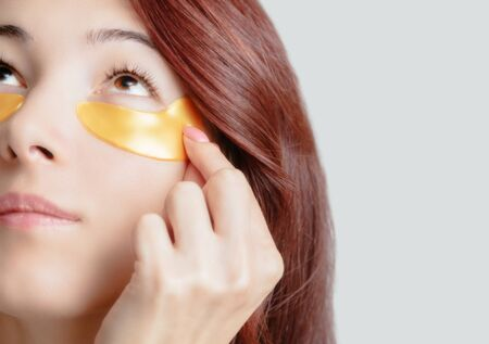 Beautiful young woman applying hydrogel golden patch under eye for healthy fresh smooth skin.
