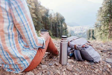Unrecognizable backpacker young woman resting with cup of tea in summer mountains.