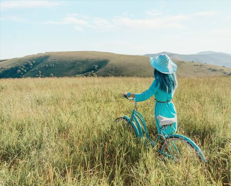 Unrecognizable romantic girl in dress and hat walking with bicycle in summer green grass meadow in summer. Stok Fotoğraf